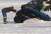 Car plunges into frozen lake